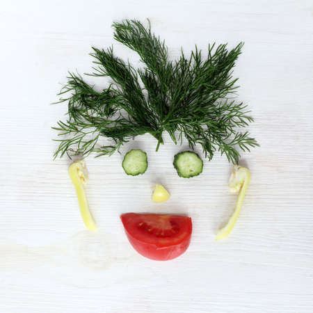 food still: flat layout of vegetables in the form of funny human face, top view  humorous still life portrait of vegetarian Stock Photo
