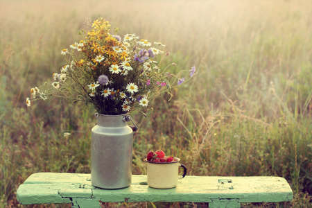 the next life: bouquet wildflowers in a can on a wooden bench standing next to a cup of strawberries  retro still life with flowers and berries in the rustic landscape