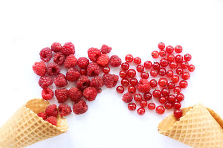 a plurality of raspberries and currants spill out of waffle cones in form of two red hearts  appetizing sweet love Stock Photo