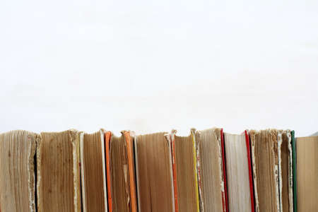 bibliomania: many old shabby books standing in a row on a light surface  used book shelf Stock Photo