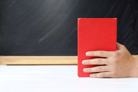 bibliomania: red book in hand, against a background of black school board  necessary literature for education Stock Photo