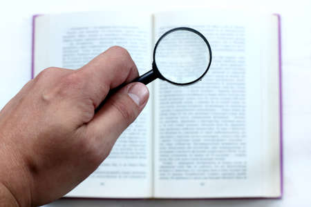 bibliomania: hand with magnifying glass on the background of an open book  thorough examination of information Stock Photo