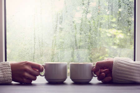 two white cups in hands on a background of wet window with raindrops / comfortable coffee break for two people 免版税图像