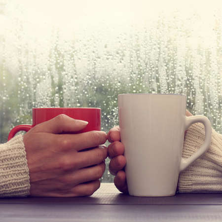two people holding red and white cups lightly touching each other in the rain outside the window / warmer together in any weather