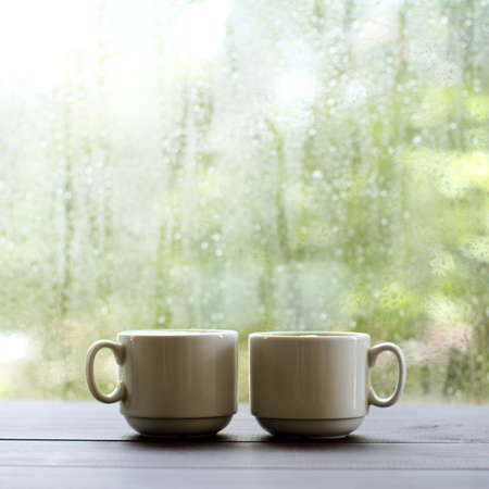 pair of white cups are on the table against the background of wet window with raindrops  warming coffee in a cozy place