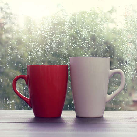 home comforts: red and white cup standing on the wooden table outside when the rain drips  warming drink in the autumn weather Stock Photo