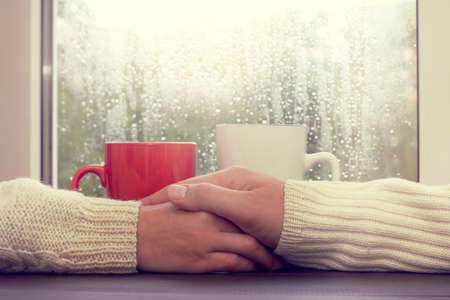 home comforts: couple people at a table, with the care relate to each other in the rain outside the window  warm relations on a date Stock Photo