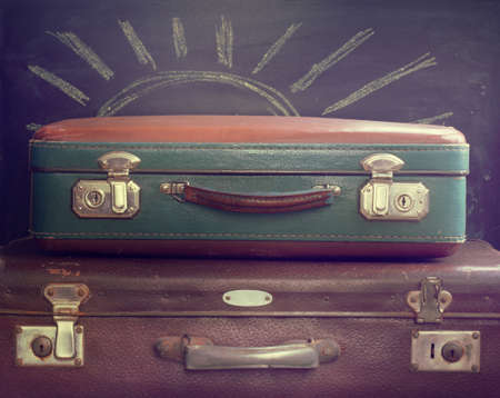 stow: vintage old suitcases for journeys on the background of blackboard painted with chalk sun  idea a warm time of year for holiday tour