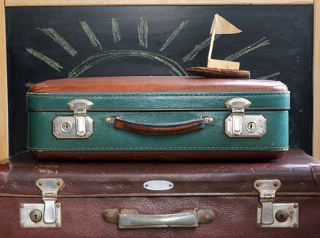 stow: retro luggage and ship made with hands on a background of the drawn chalk sun   idea of an imaginary cruise during vacation Stock Photo