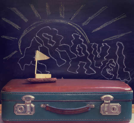 stow: retro luggage and toy sailboat made with hands on a background of the drawn chalk sun  swim time vacation