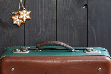 Retro suitcase and ginger gingerbread stars on wooden background / time for the Christmas travel