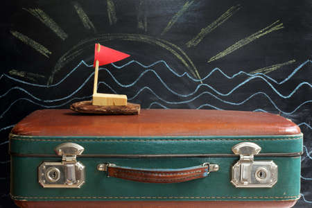 stow: old retro suitcase and ship with a red flag on a background of the sun and waves drawn in chalk on the blackboard  dream of a cruise during the holidays Stock Photo