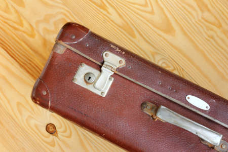 Leather worn retro suitcase standing on a light wooden background  luggage for a cruise round the world Stock Photo