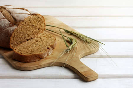 sliced dark bread lying on cutting wooden board, decorated with spikelet  traditional Russian dish