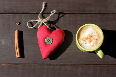 soft tissue: flat layout with cinnamon stick, frothy cappuccino and a heart of soft tissue  mystery about coffee