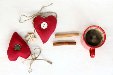 Two heart symbol with gingerbread star, cinnamon next to a mug of coffee  formula warming love