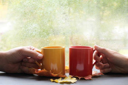 home comforts: two hands holding cups on the background of wet window with raindrops  together tastier and warmer