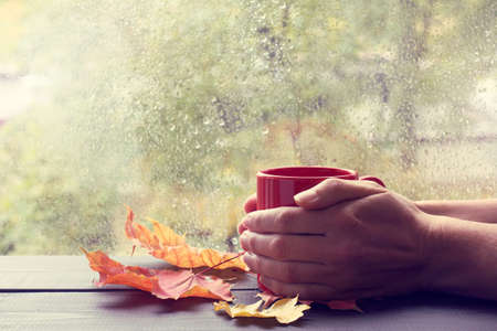 home comforts: warming his hands red hot mug against the window after the rain  autumn reinforcements strength Stock Photo