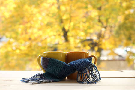 two mugs tied a warming scarf on the background of the yellowed trees outside the window  together warmer autumn