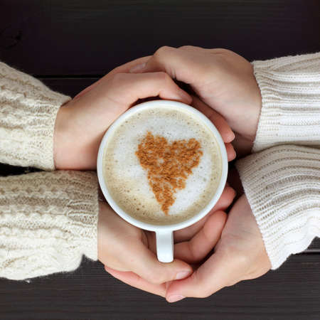 home comforts: frothy coffee with drawing heart, hands hug love people couple  share feelings together