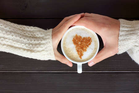 home comforts: warming cappuccino decorated a symbol heart in hands couple a top view  the two lovers in coffee