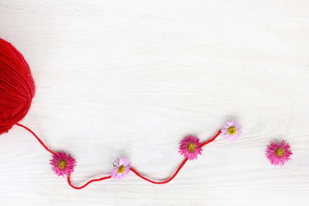 unwound a skein of thread of red color decorated with flowers  idea for fashion design Stock Photo