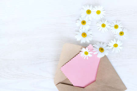 flat lay with an open letter to the paper, flying off daisies outside view from above  idea messages from your heart Stock Photo