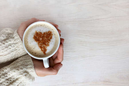 home comforts: frothy cappuccino with heart pattern in hand and dressed up warm sweater top view  love warms