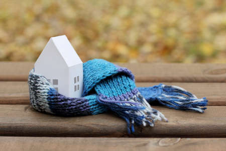 concepts with comfortable insulated house soft scarf on autumn background / time to warm the home