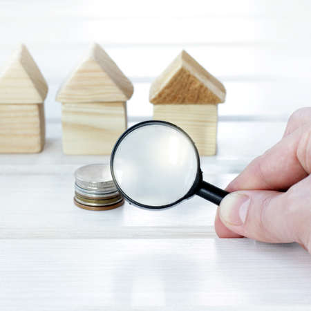 hand with magnifying glass on background pile of coins and wooden houses  attentive choice of optimal capital investment