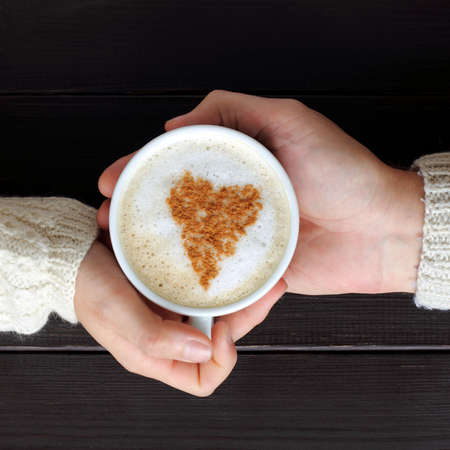 home comforts: frothy cappuccino with heart symbol in hands top view  coffee break for two