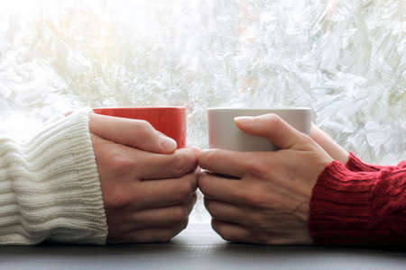 warmest: warming meeting couple in love pair on a background of frozen window with a winter pattern  share warmest feelings Stock Photo