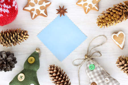 flat layout of the blue sheet for inscriptions surrounded by trees, cones and holiday cookies top view  decorations for Christmas and New Year