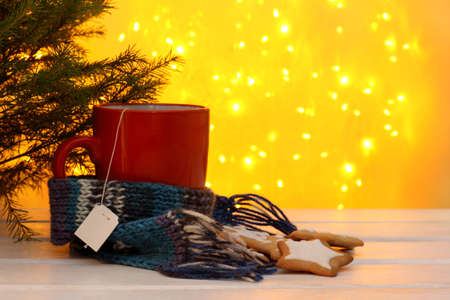 home comforts: red cup with tea labels, cookies, scarf and Christmas tree on the background of holiday lights  home welcoming atmosphere for winter holidays