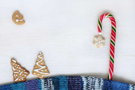 flat layout of the scarf with ginger cookies patterned and striped candy on light background  Christmas fairy tale forest