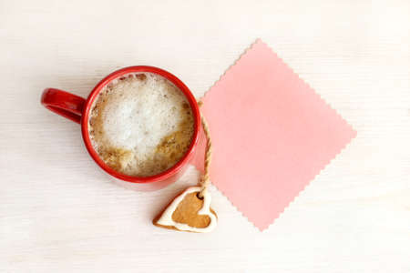 coffee and carrot shaped sheet to write on a bright background of the table top view  favorite warming drink