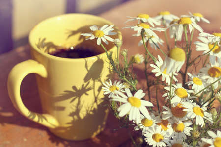 field of daisies: Black coffee in yellow mug and a bouquet of field daisies on a sunny day  coffee break in the fresh air