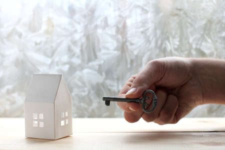 breadboard model the house from a paper and hand with key on a background of the freezing window  effective solutions for all situations
