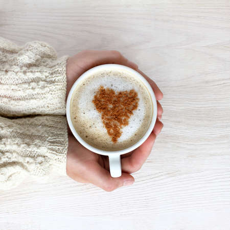home comforts:  heart symbol decorate frothy cappuccino in a white cup in his hand  favorite coffee with mood