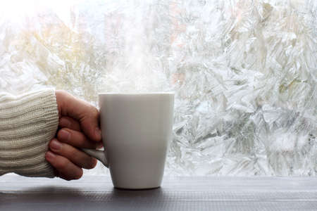 home comforts: white mug with a hot drink in hand dressed in a sweater against the window with frosty patterns  warming in winter Stock Photo