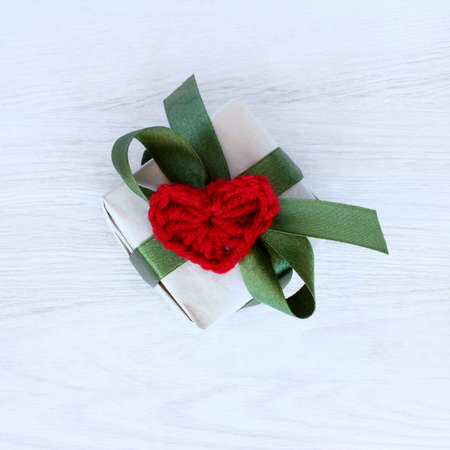 Holiday gift with green ribbon and red soft heart symbol top view  surprise in Day of Love