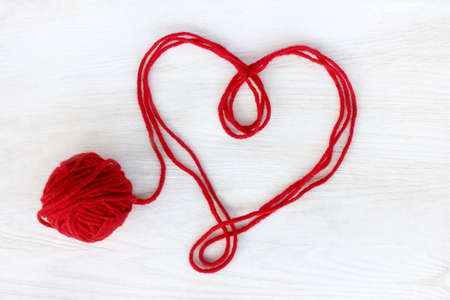 hilo rojo: heart symbol of red thread on a light wooden surface top view  untied love affection
