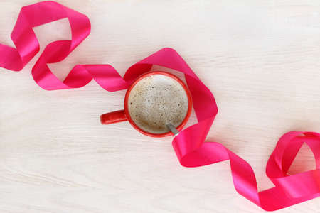 flat lay with red mug of frothy coffee and flowing ribbon top view  break with a delicate aroma of cappuccino Stock Photo