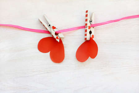 retained: couple of paper hearts hanging on pink ribbon retained by clothespins  special power of love