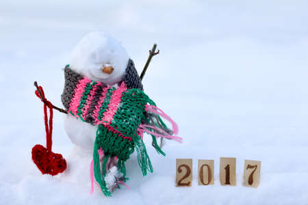 amorous snowman in a warm scarf on the background of snowy landscape  celebration day enamored 2017