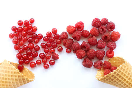 impassioned: red berries are strewed out of waffle cones in the form of hearts on a light wooden table  impassioned meeting day of lovers