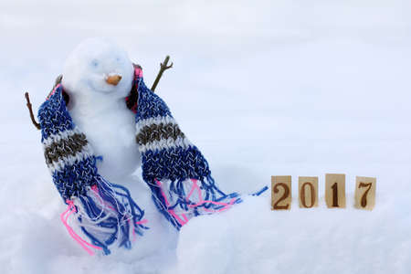 smiling snowman in the scarf next to numbers in the snowdrift  happy winter vacation