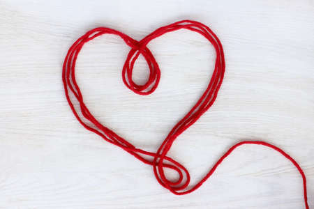 heart symbol of the red threads lying on a light wood surface top view  festive Valentine