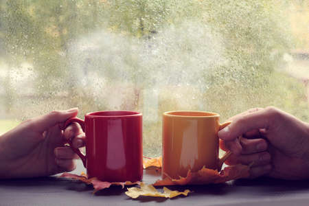 home comforts: meeting couples in love during a coffee break against the window with rain drops  romantic love story Stock Photo