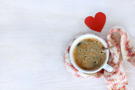 hot coffee in a mug wrapped a scarf, and a heart symbol, top view  favorite beverage warms